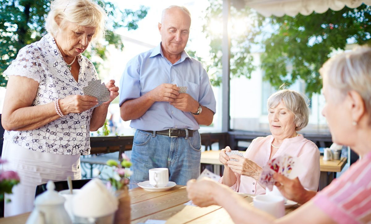 Restful seniors playing cards in outdoor cafe at leisure