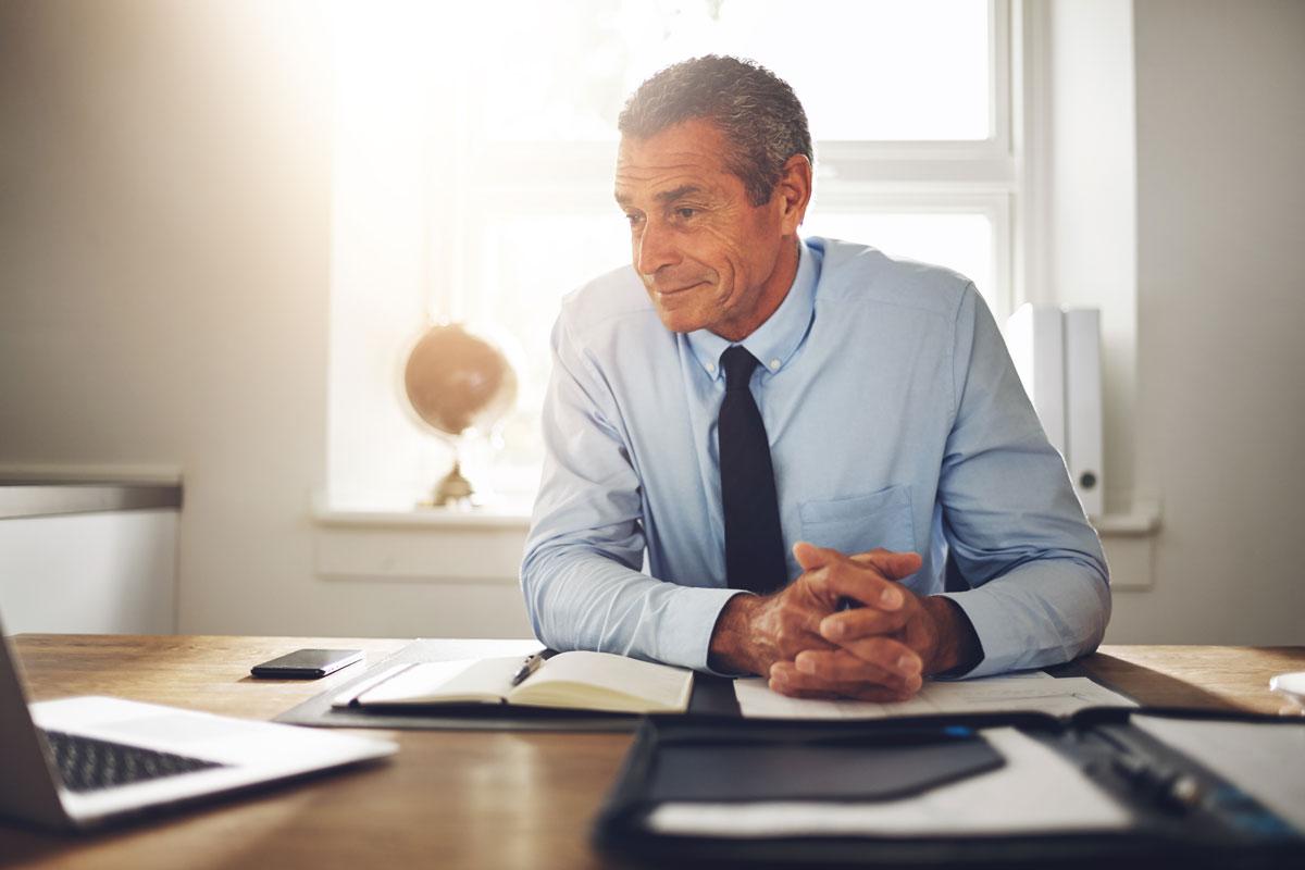 seniorman sitting at work desk: supplementing income