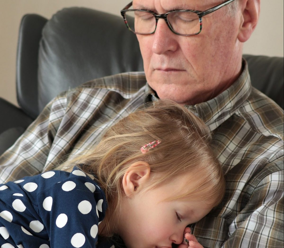 child girl sleeping in her grandfather's arms