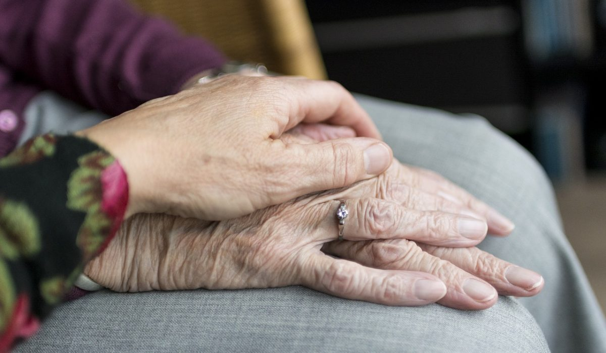 Hands of two elderly people being supportive