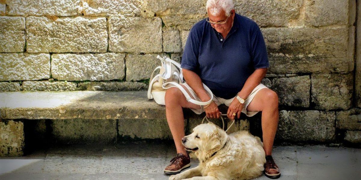 Elderly man sitting with his dog