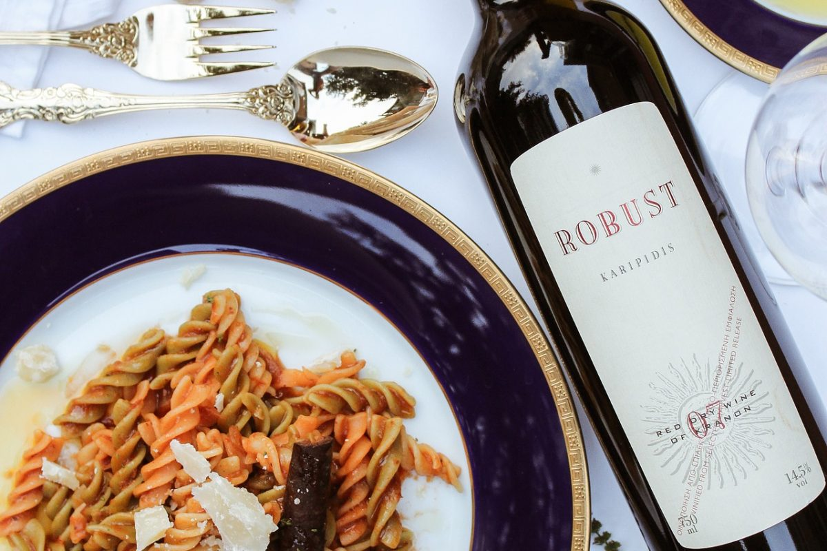 Pasta dish with a bottle of red wine on a table