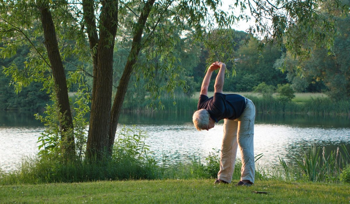 Old man stretching on the grass near a lake