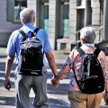 senior couple holding hands walking with back packs