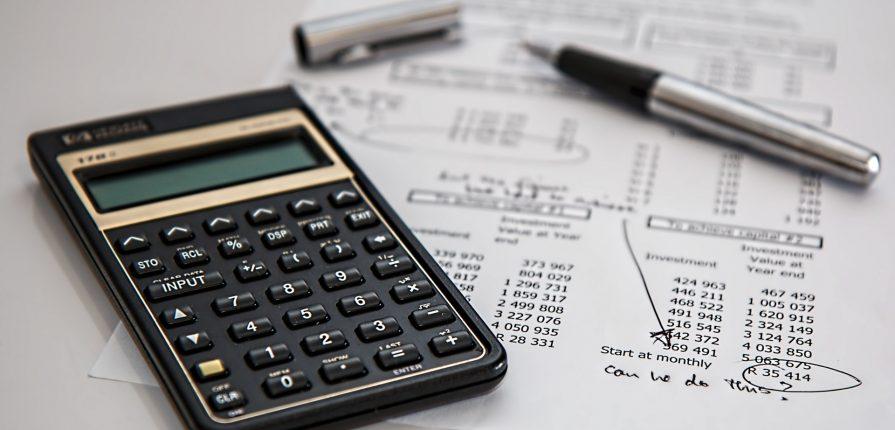 Calculator next to bills financial preparation for retirement