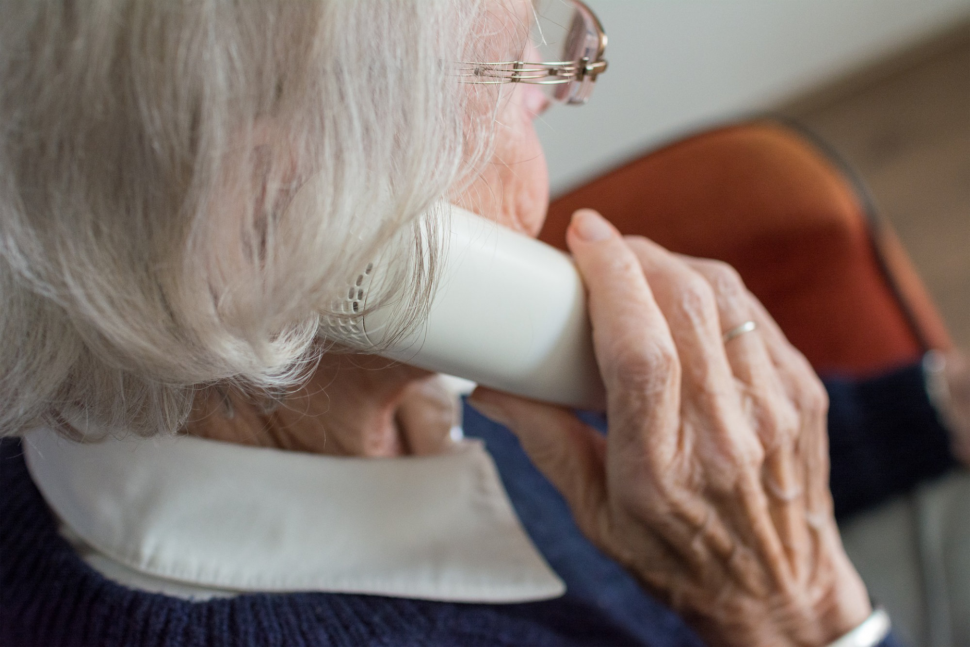elderly woman holding telephone to her ear
