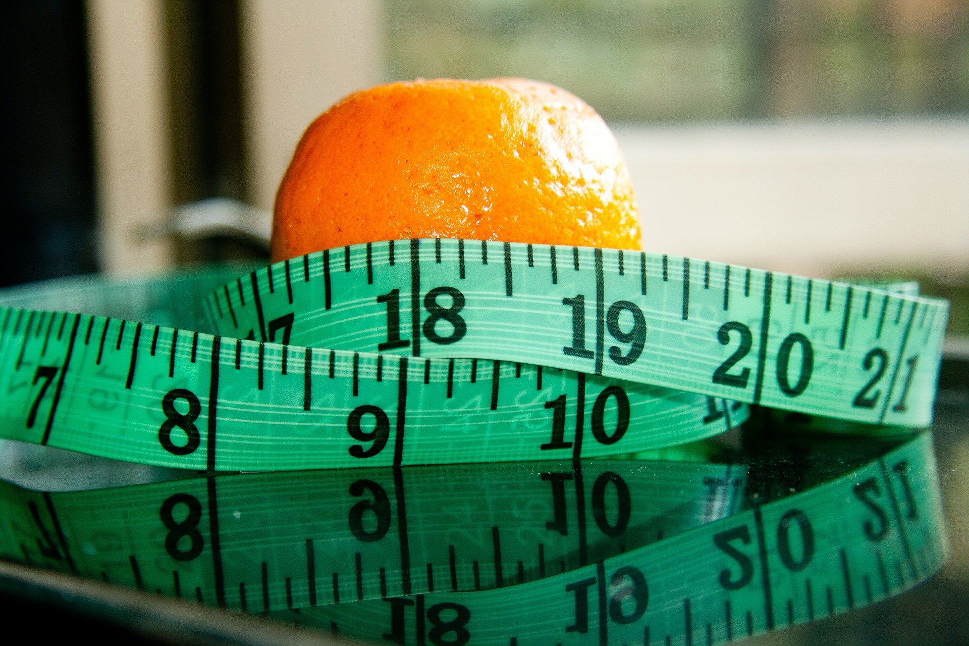 healthy ageing - tape measure and an orange