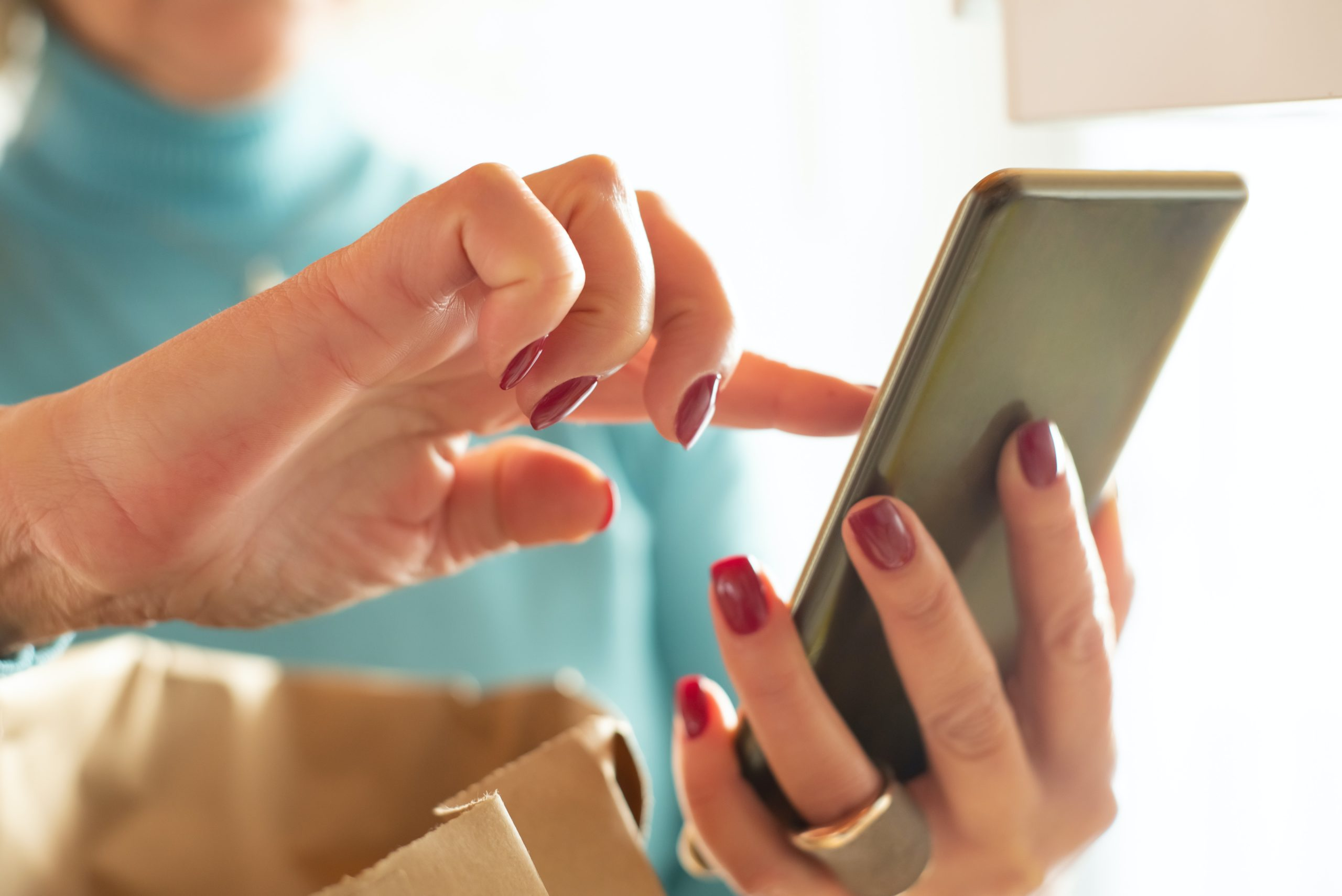 woman tapping cell phone with hand