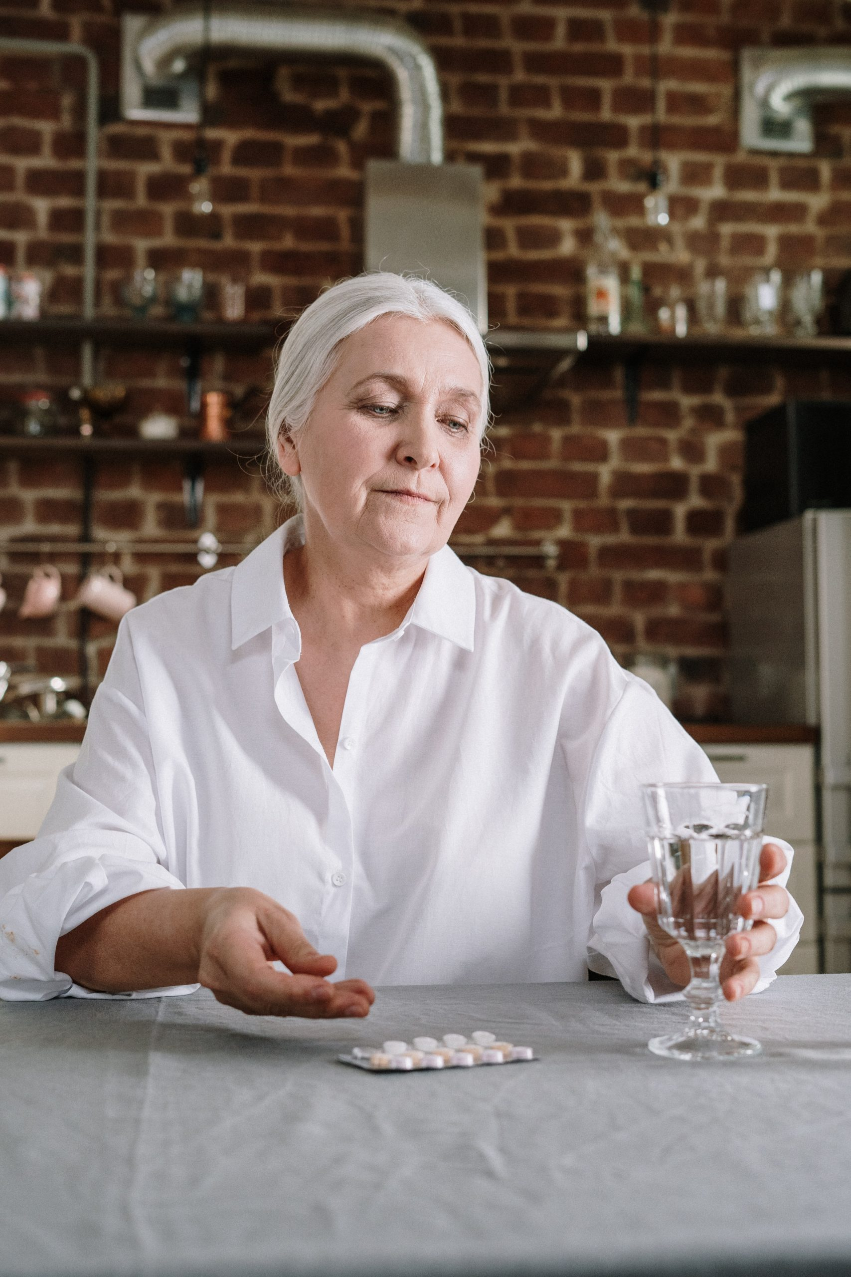woman holding glass of water and pills sitting at kitchen bench