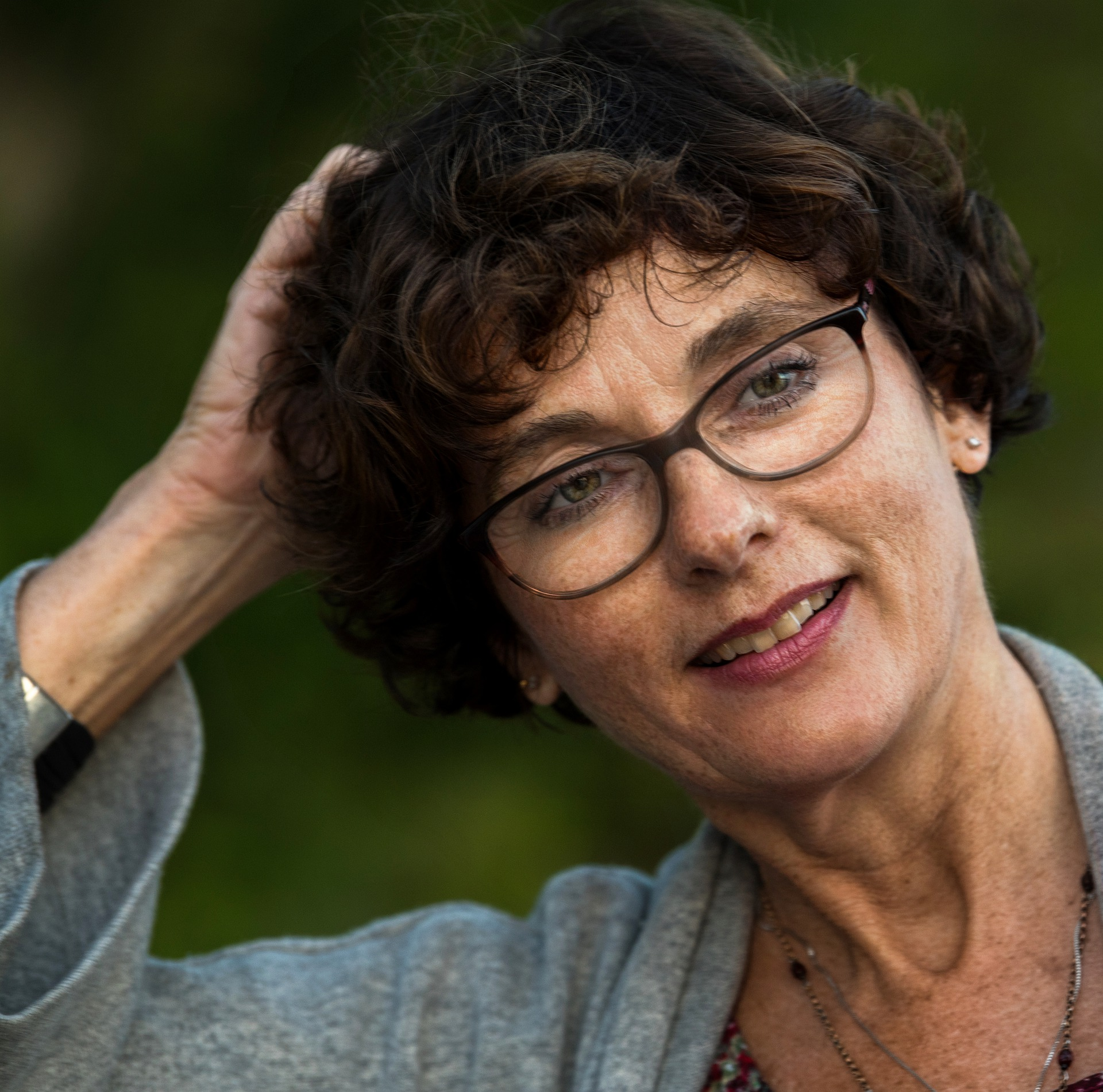 woman with curly hair and glasses